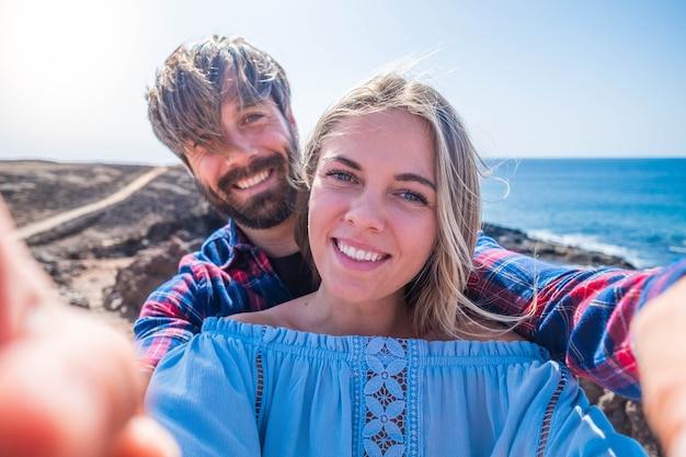 Coppia di adulti e fidanzati che si fanno un selfie insieme con le loro quattro mani - due persone innamorate che tengono il telefono insieme alla spiaggia sullo sfondo