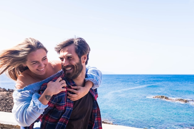 Coppia di adulti che si divertono insieme ridendo e sorridendo - mare o oceano sullo sfondo - uomo e donna innamorati che si incontrano insieme