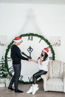 Coppia contro il grande orologio che mostra la mezzanotte del nuovo anno
