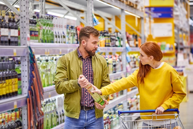 Coppia litigando nel reparto alcolici nel supermercato, maschio vuole comprare un po 'di alcol, la donna è arrabbiata con la sua scelta, insoddisfatta