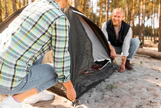 Coppie che organizzano una tenda nella natura