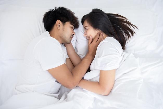 Coppia uomo asiatico e donna sul letto in camera da letto bianca