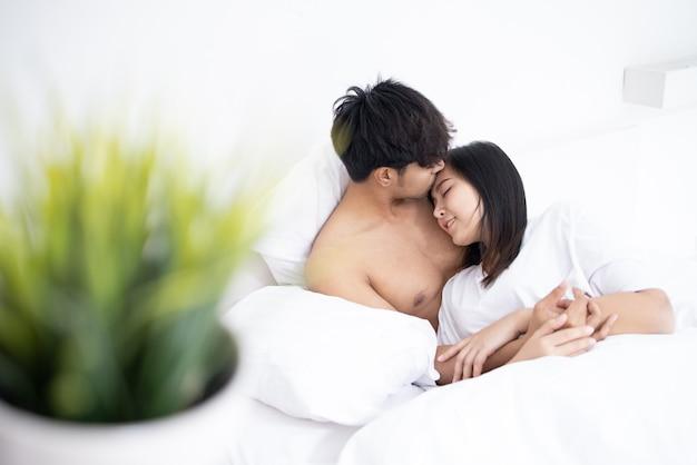 Coppia uomo asiatico e donna sul letto in camera da letto bianca Foto Premium