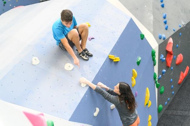 Coppia di atleti scalatore salendo su roccia ripida, arrampicata su parete artificiale al chiuso. sport estremi e concetto di bouldering