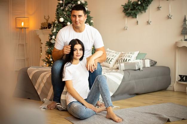 Coppia in camera da letto con decorazioni natalizie. l'uomo abbraccia la femmina.