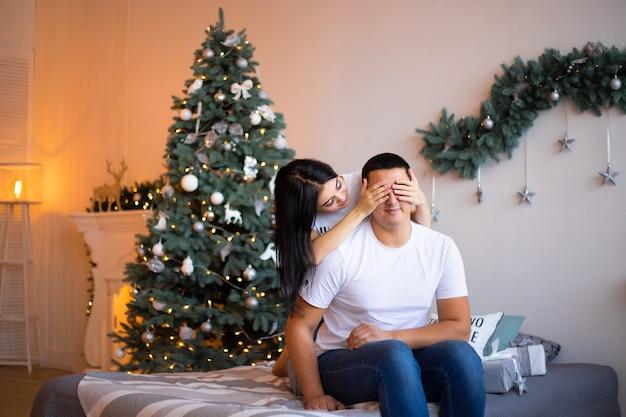 Coppia in camera da letto con decorazioni natalizie.
