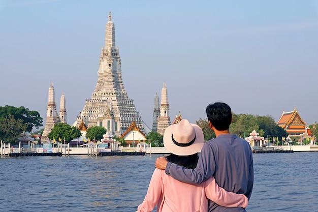 Giovane essendo impressionato dal tempio dell'alba o wat arun, il punto di riferimento iconico situato sulla riva del fiume chao phraya, bangkok, thailandia