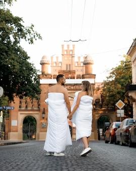 Una coppia con le coperte in giro per la città