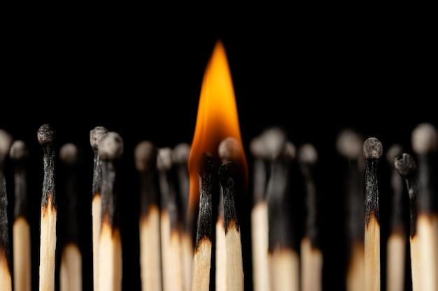 Coppia di fiammiferi bruciati in piedi uno accanto all'altro con un piccolo fuoco sopra di loro