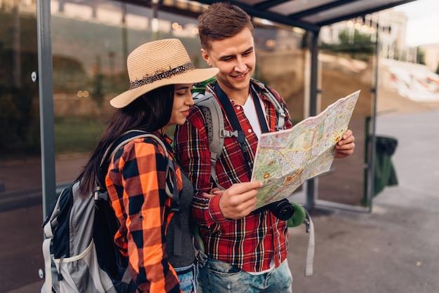 Coppia alla fermata dell'autobus studia la mappa delle attrazioni della città, escursione in località turistica. escursioni estive. escursione all'avventura di un giovane uomo e una donna