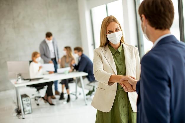 Coppia di uomini d'affari che si stringono la mano in ufficio e indossano maschere protettive a causa dell'epidemia di coronavirus