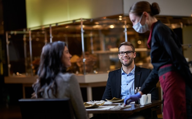 Coppia di uomini d'affari seduti al tavolo del ristorante e fissando il server mentre lei mette delle posate