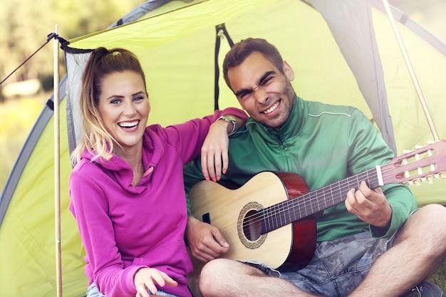 Coppia che si accampa nella foresta e suona la chitarra