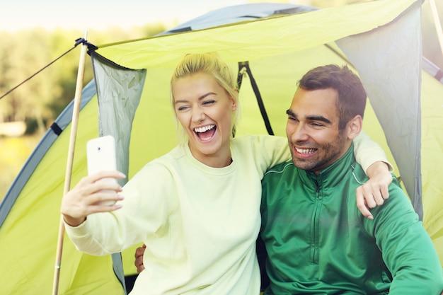 Coppia che si accampa nella foresta e si fa un selfie