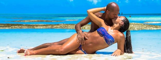 Coppia alla spiaggia caraibica sull'immagine dell'insegna di vacanza con lo spazio della copia