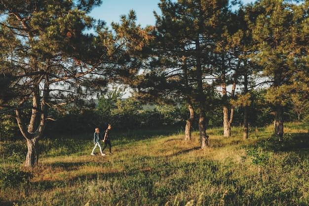 Coppia in abiti casual camminando sull'erba verde tra grandi pini illuminati dal sole che tengono le mani in estate dalla distanza