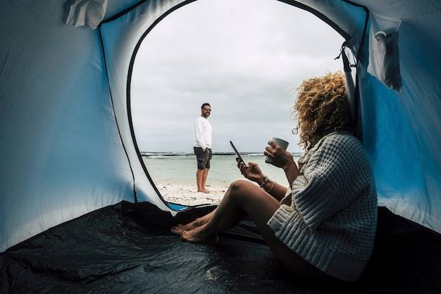 Coppia di viaggiatori caucasici in campeggio sulla spiaggia vicino allo stile di vita alternativo di vacanza paradiso delle onde dell'oceano con piccola casa e godersi l'attività di svago all'aperto