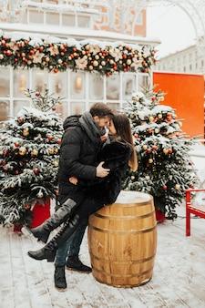 Coppie che celebrano le vacanze invernali all'aperto in un mercatino di natale