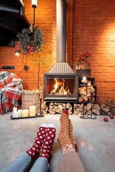 Coppia in calze di natale davanti al caminetto a casa. il concetto di comfort durante le vacanze invernali e di capodanno