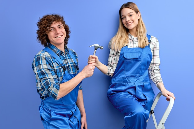 Coppia di caposquadra costruttori, uomo e donna in uniforme che ripara utilizzando strumenti
