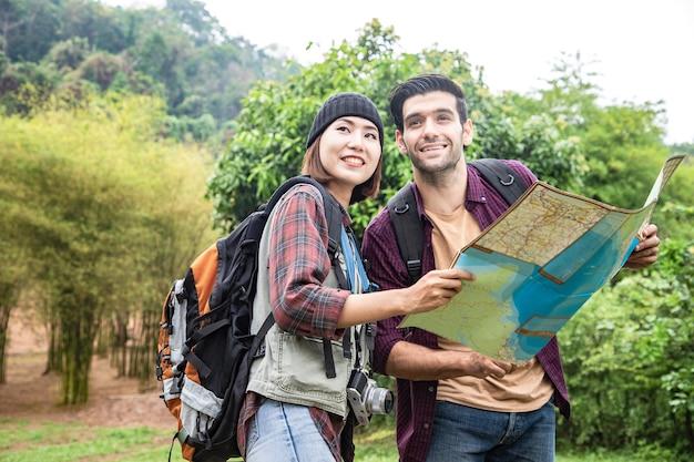 Coppia cari amici che tengono la propria mappa di disegno in viaggio verso le attrazioni naturali e il parco pubblico vicino alla montagna
