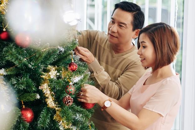 Coppia che decora l'albero di natale