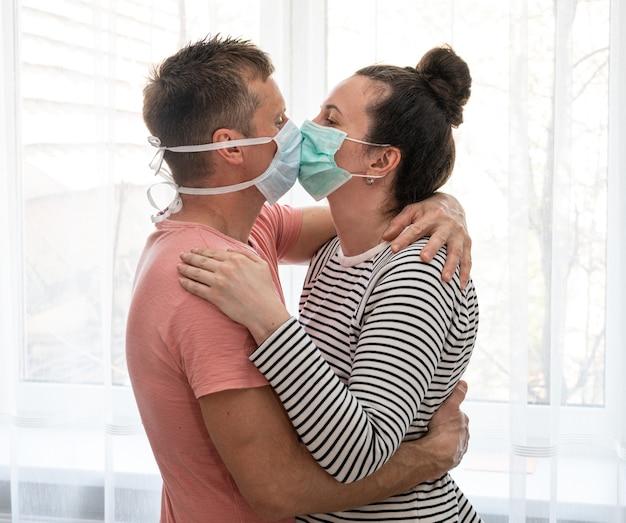 Coppia in maschere usa e getta baciarsi vicino alla finestra a casa