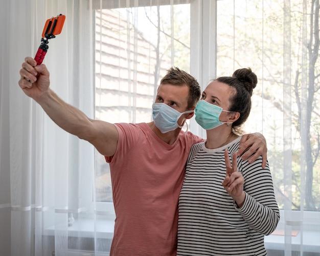Coppia in maschere usa e getta prendendo selfie a casa