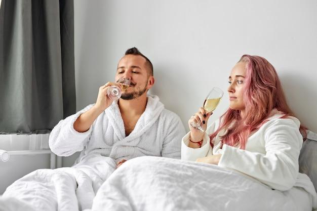 Coppia bere spumante, uomo caucasico e donna riposano indossando vestaglia bianca a casa