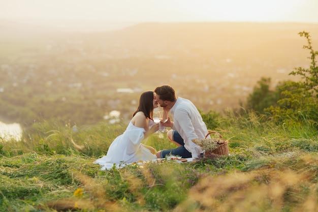 Coppia che beve vino e si bacia durante un picnic in un campo