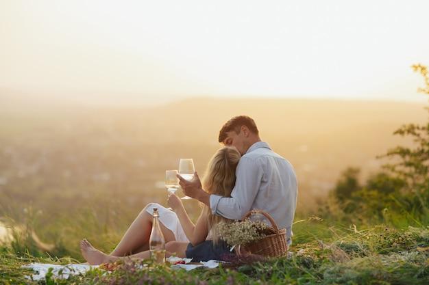 Coppia che beve vino a un picnic in un campo