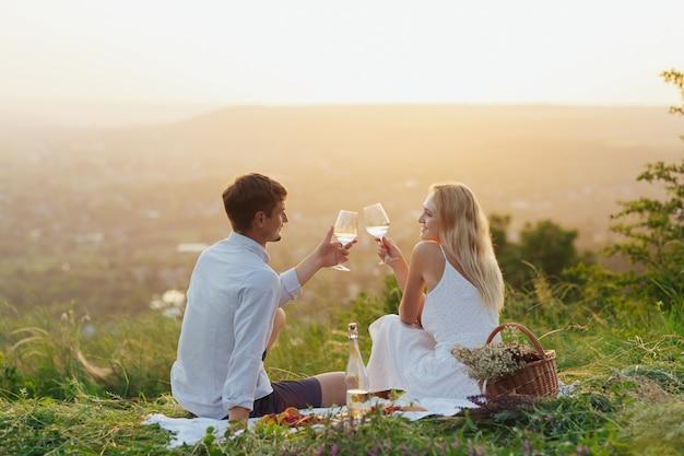 Coppia bevendo vino e brindando a un picnic in un campo Foto Premium