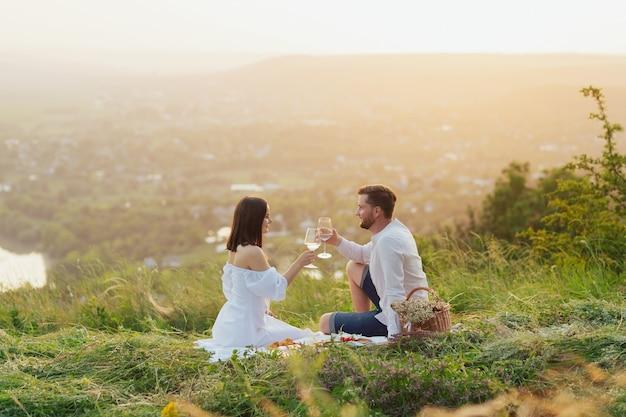 Coppia bevendo vino e brindando a un picnic in un campo