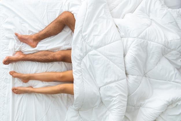 La coppia sotto il piumone sdraiato sul letto. vista dall'alto