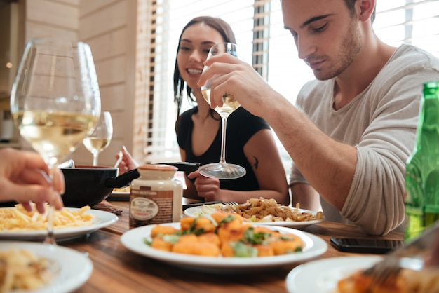 Coppia mangiare e bere vino con gli amici in cucina