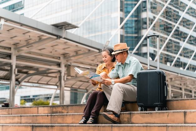 Una coppia di anziani turisti asiatici che visitano la capitale allegramente divertendosi e guardando la mappa per trovare luoghi da visitare.