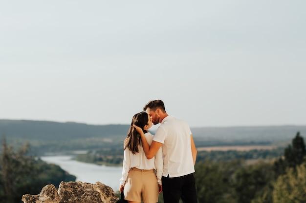 Coppia abbracciare e baciare sulla collina con un paesaggio incredibile.