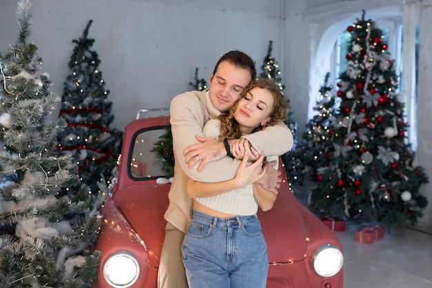 Coppia godendo il loro tempo insieme vicino all'auto rossa. albero di natale sullo sfondo. luci magiche