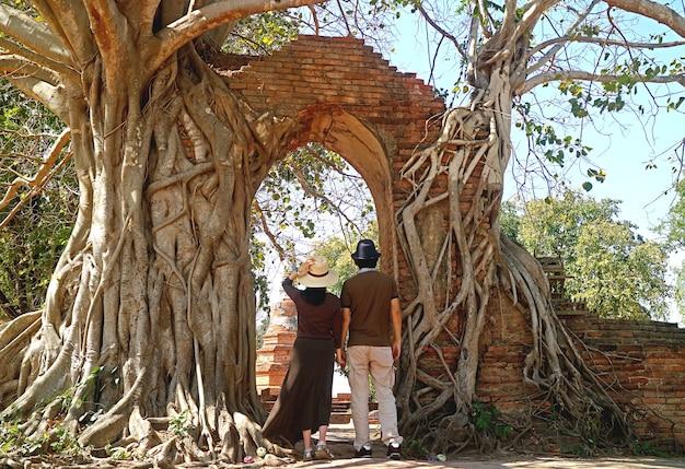 Coppia che entra nell'incredibile porta del tempo delle rovine del tempio di wat phra ngam ad ayutthaya, thailandia