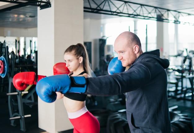 Coppia esercitando la punzonatura. una giovane donna e un uomo stanno allenando pugni in guantoni da boxe in palestra
