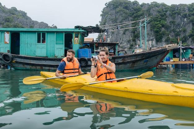 Coppia che esplora il villaggio galleggiante in kayak e scatta foto in barca. baia di halong, vietnam, isola di cat ba