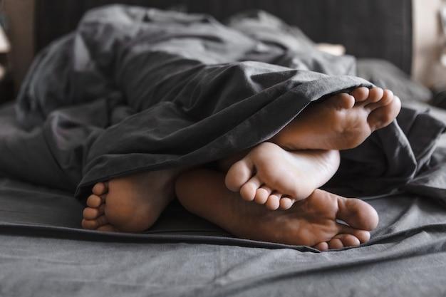 Un paio di piedi sotto la coperta a letto con lenzuola grigie si chiudono sullo spazio della copia