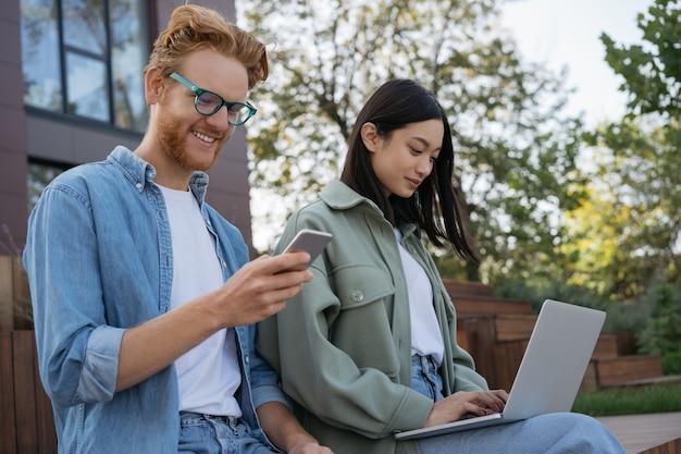 Coppia di liberi professionisti utilizzando il telefono cellulare del computer portatile che lavora da casa