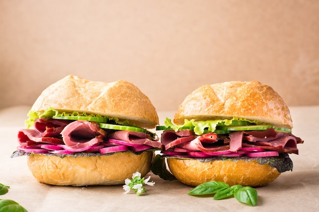 Un paio di hamburger freschi con pastrami, cetriolo, ravanello ed erbe aromatiche su carta artigianale. fast food americano. copia spazio