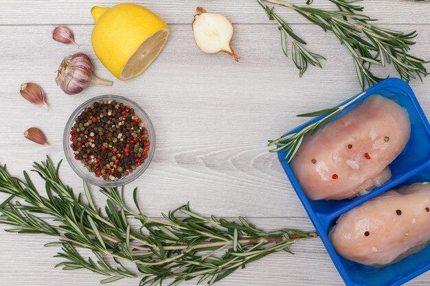Coppia di petti di pollo crudo fresco o filetto in contenitore di plastica con aglio, cipolla, limone, peperoni pimento in ciotola di vetro e rosmarino su un fondo di legno. vista dall'alto.