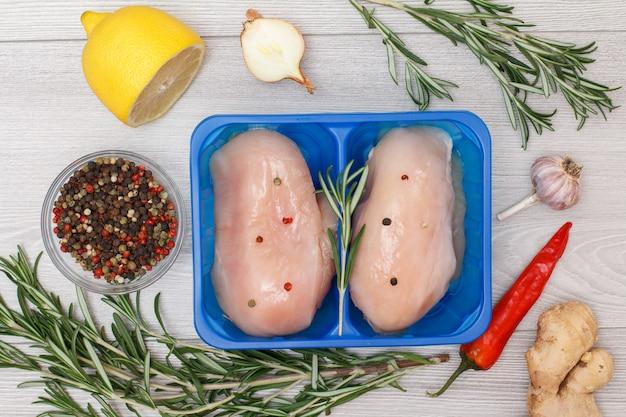 Coppia di petti di pollo crudo fresco o filetto in contenitore di plastica con radice di zenzero, peperoncino, aglio, cipolla, limone, peperoni pimento in ciotola di vetro e rosmarino su fondo di legno. vista dall'alto.
