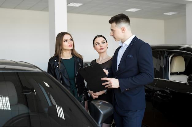 Coppia di amici di womans con un concessionario di auto sceglie un'auto in una concessionaria di auto
