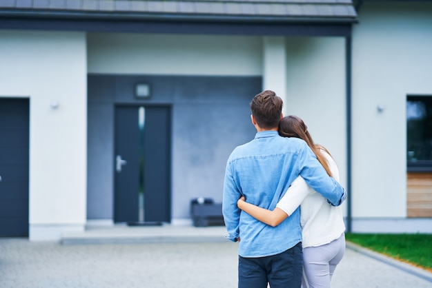 Coppia davanti a casa unifamiliare in moderna zona residenziale