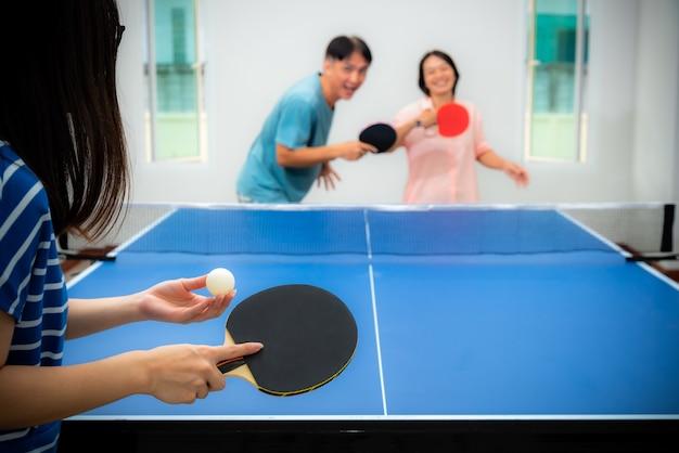 Coppia divertente giocando a ping pong o ping pong indoor insieme per il tempo libero con la competizione in giochi sportivi a casa. padre, madre e figlia, la famiglia asiatica si godono l'esercizio ricreativo e restano a casa in thailandia