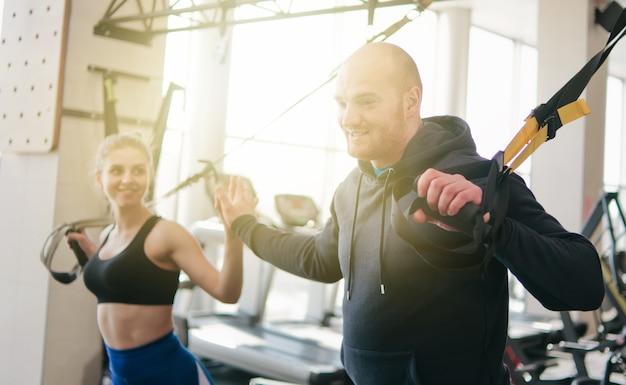 Coppia allenamento funzionale. dammi il cinque. donna e uomo che fa esercizio con cinghie di fitness in palestra. allenamento funzionale